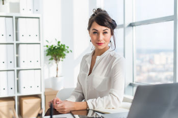 Close-up portrait of a woman sitting in modern loft office, smiling, looking at camera. Young confident female business worker ready for the work day