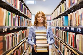 people, knowledge, education and school concept - happy student girl or young woman with stack of books in library